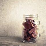 Pedazos del chocolate en la botella de cristal Foto de archivo