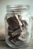 Pedazos del chocolate en la botella de cristal Imagenes de archivo