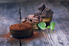 Pedazos del chocolate, polvo de cacao y granos de cacao oscuros imagen de archivo libre de regalías