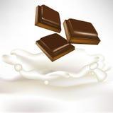 Pedazos del chocolate que caen en leche Imágenes de archivo libres de regalías