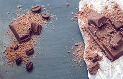 Pedazos del chocolate y polvo de cacao quebrados en el fondo y la hoja de piedra Imágenes de archivo libres de regalías