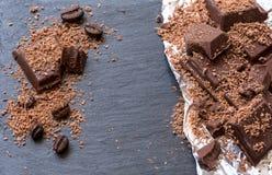 Pedazos del chocolate y polvo de cacao quebrados en el fondo y la hoja de piedra Imagen de archivo