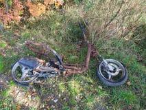 Pedazos del ciclomotor abandonados en naturaleza Fotos de archivo libres de regalías