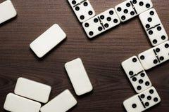 Pedazos del dominó en el fondo de madera de la tabla Foto de archivo libre de regalías