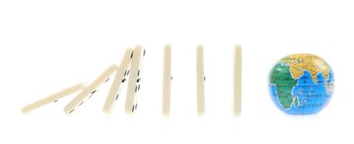 Pedazos del dominó que caen encendido al globo Foto de archivo