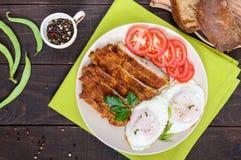 Pedazos del escalope de la tajada, tostada con los huevos, tomate fresco en un fondo de madera oscuro Imagen de archivo