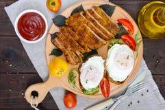 Pedazos del escalope de la tajada, tostada con los huevos, tomate fresco en un tablero de madera Fotografía de archivo libre de regalías
