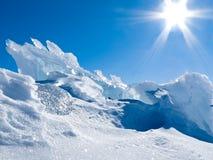 Pedazos del hielo del glaciar con nieve y el cielo azul soleado Foto de archivo