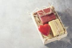 Pedazos del jabón hecho a mano natural y del ` rojo s en una caja de madera, idea de la tarjeta del día de San Valentín para un r Foto de archivo libre de regalías
