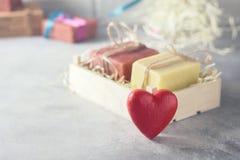 Pedazos del jabón hecho a mano natural y del ` rojo s en una caja de madera, idea de la tarjeta del día de San Valentín para un r Fotografía de archivo libre de regalías
