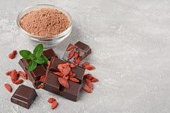 Pedazos del primer de barra de chocolate oscura con las bayas secadas de Goji, el bol de vidrio de polvo de cacao y la menta fotos de archivo