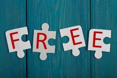 Pedazos del rompecabezas con el texto y x22; FREE& x22; en fondo de madera azul Imágenes de archivo libres de regalías