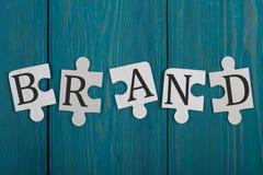 Pedazos del rompecabezas con palabra y x22; Brand& x22; foto de archivo libre de regalías