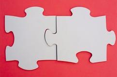 Pedazos del rompecabezas de rompecabezas en el paño rojo Fotos de archivo libres de regalías