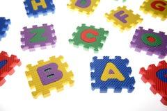 Pedazos del rompecabezas del alfabeto Imágenes de archivo libres de regalías