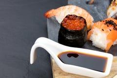 Pedazos del sushi en la tabla de la pizarra Imagenes de archivo