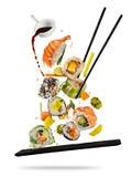 Pedazos del sushi puestos entre los palillos en el fondo blanco Fotos de archivo