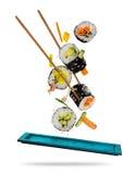Pedazos del sushi puestos entre los palillos en el fondo blanco Foto de archivo