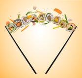Pedazos del sushi puestos entre los palillos, en fondo coloreado Fotos de archivo libres de regalías