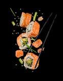 Pedazos del sushi puestos entre los palillos en fondo negro Imagenes de archivo