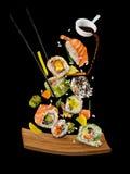 Pedazos del sushi puestos entre los palillos en fondo negro Imagen de archivo