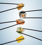 Pedazos del sushi puestos entre los palillos, en fondo suave Foto de archivo libre de regalías