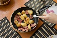 Pedazos fritos de patatas de oro cocidas y de brillante rojo, de molte Imagen de archivo