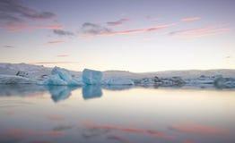 Pedazos gigantes de hielo que fluyen en y que reflejan en el lago frío con un detrás glaciar enorme, laguna glaciar del jokulsarl Imagenes de archivo