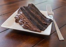 Pedazos grandes de torta de chocolate en la placa blanca con la bifurcación Imagen de archivo