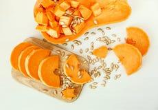 Pedazos grandes del corte de calabaza con las semillas en el tablero de madera Harves Foto de archivo libre de regalías