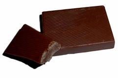Pedazos mordidos de chocolate, aislados en blanco Imágenes de archivo libres de regalías