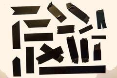 Pedazos negros de la cinta imagenes de archivo
