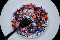 Pedazos plásticos multicolores machacados en la placa y la bifurcación blancas Foto de archivo libre de regalías