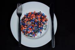 Pedazos plásticos multicolores machacados en la placa y los cubiertos blancos Imagen de archivo libre de regalías