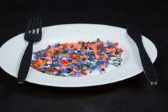 Pedazos plásticos multicolores machacados en la placa y los cubiertos blancos Foto de archivo libre de regalías
