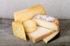 Pedazos principales y diversos de queso en una tabla de madera Foto de archivo