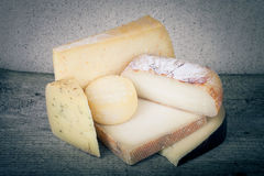 Pedazos principales y diversos de queso en una tabla de madera teñido Imagenes de archivo