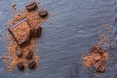 Pedazos quebrados del chocolate y chocolate rallado en el fondo de piedra Copia-spase Imagen de archivo