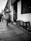 A peddler. A senior peddler is saling vegetables at home door in countryside, China Royalty Free Stock Image