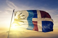 Pedernales Province of Dominican Republic flag textile cloth fabric waving on the top sunrise mist fog. Beautiful royalty free stock photo