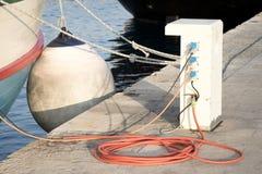 Pedestal del abastecimiento eléctrico y de agua en un embarcadero con la manguera y el taxi foto de archivo libre de regalías