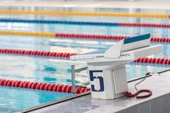 Pedestal para los nadadores en la piscina interior foto de archivo libre de regalías