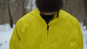 Pedestal shot of bearded hipster caucasian male with blue eyes in winter forest. Sporty fit man with earphones standing in snowy wood. outdoor activities stock video