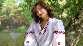 Attractive woman in ethnic ukrainian dress sitting on birch tree near river. Pedestal shot of woman in ethnic ukrainian dress holding floral circlet outside stock video