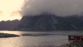 Pedestal up time lapse of clouds swirling round the mountains, Lofoten Islands stock video
