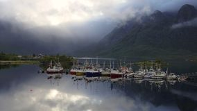 Pedestal up time lapse of moored boats and clouds swirling round the mountains stock footage