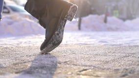 Pedestre do pé que anda no gelo polvilhado com o fim antiderrapante do reagente acima, mo lento