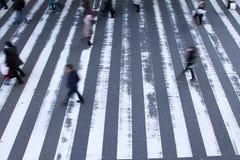 Pedestres borrados que apressam-se através da faixa de travessia Fotografia de Stock Royalty Free