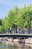 Pedestres em uma ponte com bicicletas estacionadas, Amsterdão, Países Baixos Imagens de Stock