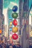 Pedestres que andam para a uma avenida ocupada icónica do quadro de avisos do Times Square para baixo 7a em Manhattan central Fotografia de Stock